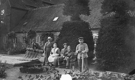 Yderst til venstre i billedet ses en mand med en sivmåtte. I de gamle haver blev der hele tiden fremstillet sivmåtter. De blev brugt til at dække for mistbænke og også brugt til at bygge praktiske og smukke læskærme med.