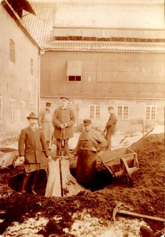 Garvemester Bloch og medarbejdere henter færdig garvet skind fra gruben i gården. I dag er der beboelse i komplekset.