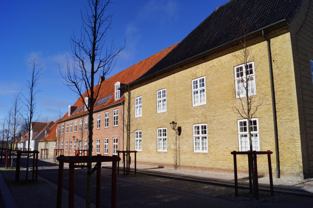 Skolen med de røde mursten ses i fortsættelse af kirkebygningen. Er opført i 1788.
